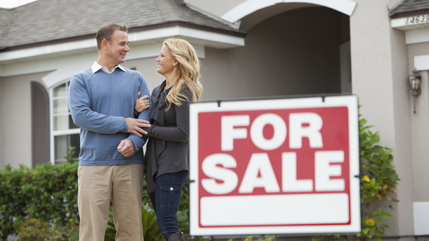 Couple standing in front of house for sale